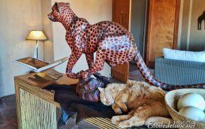 Un chat, bien heureux au pied du symbole de Bagatelle : le guépard